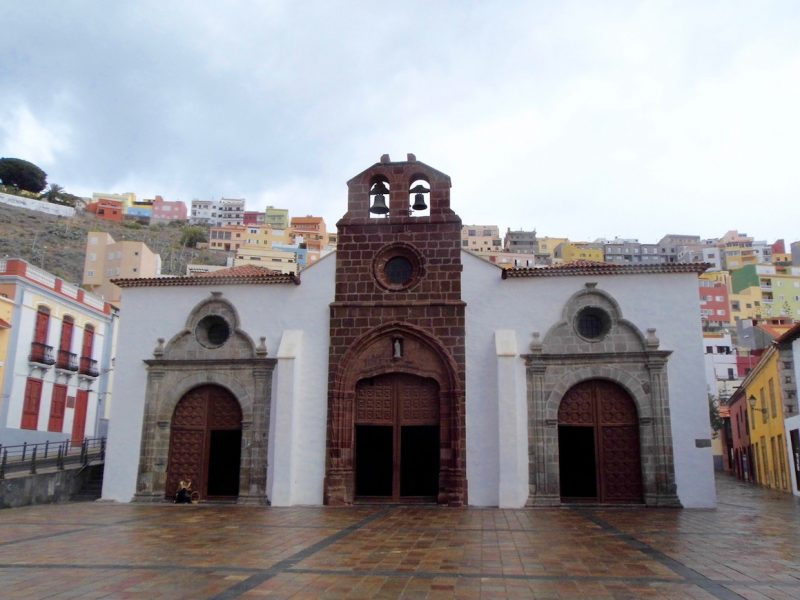 La Gomera: Church in San Sebastian with colourful houses on hills.