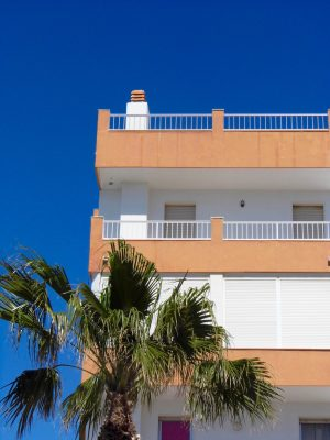 The streets of La Herradura, Spain: Orange apartment set against bright blue sky.